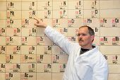 Chemistry teacher pointing at periodic table