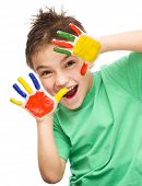 Portrait of a cute cheerful boy showing her hands painted in bright colors, isolated over white