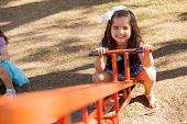 stock photo of seesaw  - Beautiful little brunette on the bottom of a seesaw in a park - JPG