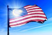 stock photo of waving  - Malaysia flag waving on the wind on blue sky - JPG