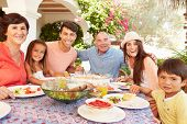 picture of multi-generation  - Multi Generation Family Enjoying Meal On Terrace Together - JPG