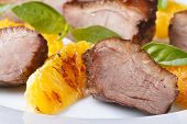 foto of roast duck  - slices of roasted duck meat with orange and basil macro horizontal on a white plate - JPG