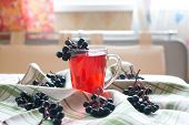 stock photo of chokeberry  - Compote of black chokeberry on the table - JPG