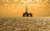 foto of oil derrick  - Oil rig during sunset in Baku - JPG