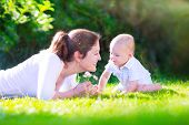 image of mother baby nature  - Happy beautiful woman young mother playing with her adorable baby son cute little boy enjoying together a sunny warm day playing on the lawn in a summer garden - JPG