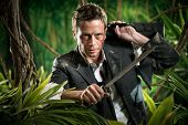 picture of machete  - Confident strong businessman dealing with jungle dangers holding a machete - JPG