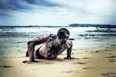 stock photo of gruesome  - young man with a zombie body painting - JPG