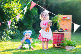 picture of little sister  - Funny curly little girl and adorable baby boy cute brother and sister playing together with a vintage wooden toy kitchen table ware and fresh healthy vegetables in a sunny summer garden - JPG