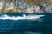 foto of phi phi  - a speed boat passing near a cliff in Phi Phi Island Thailand - JPG