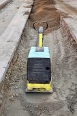 stock photo of vibration plate  - Vibratory plate compactor compacting sand at road construction site - JPG