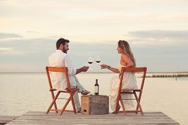 picture of jetties  - Woman and man couple drinking red wine at the seaside on a jetty - JPG