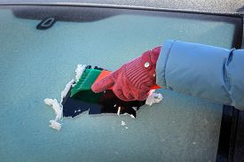 picture of scrape  - Winter scene human hand in glove scraping ice from windshield of car - JPG