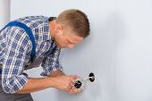 picture of electric socket  - Young Electrician Installing Electrical Socket On Wall In House - JPG