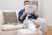picture of disability  - Disabled Man With Crutches Sitting On Sofa Reading Newspaper - JPG
