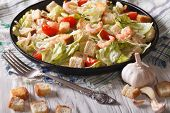 stock photo of caesar salad  - Fresh Caesar salad with shrimp and tomatoes close up on black plate - JPG