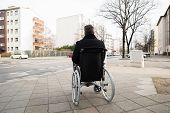 stock photo of disability  - Rear View Of A Disabled Man On Wheelchair Looking At Street - JPG