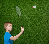 foto of shuttlecock  - Happy boy holding badminton racket and shuttlecock over green grass - JPG