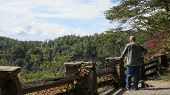 stock photo of split rail fence  - Man resting hand on stone and wood split rail fence while looking at scenic view - JPG