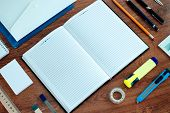 picture of neat  - High Angle View of Office or School Supplies Arranged Neatly Around Notebook Open to Blank Page on Wooden Desk Surface - JPG