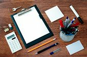 picture of neat  - High Angle View of Office or School Supplies Arranged Neatly Around Clipboard with Blank Page on Wooden Desk Surface - JPG