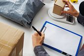 stock photo of argo  - Post Office worker weighs the parcel before sending - JPG