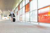 pic of carry-on luggage  - Full length of young businesswoman with luggage rushing in railroad station - JPG