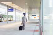 pic of carry-on luggage  - Full length rear view of businessman with luggage walking in railroad platform - JPG