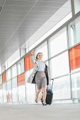 picture of carry-on luggage  - Full length of young businesswoman with luggage rushing in railroad station - JPG