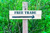 foto of free-trade  - FREE TRADE written on Directional wooden sign with arrow pointing to the right against green leaves background - JPG