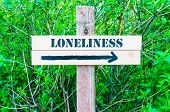 foto of loneliness  - LONELINESS written on Directional wooden sign with arrow pointing to the right against green leaves background - JPG