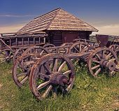 picture of abandoned house  - the remains of wooden carts on the background of abandoned wooden houses - JPG