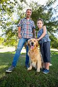 picture of dog park  - Father and daughter with their pet dog in the park on a sunny day - JPG