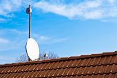 foto of red roof  - detail of satellite dish on the red roof - JPG