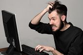 foto of keyboard  - Funny and crazy man using a computer on gray background - JPG