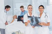 stock photo of x-files  - Smiling doctors discussing about patients file in hospital room - JPG
