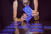 pic of fortune-teller  - Fortune teller forecasting the future with tarot cards on black background - JPG