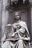 stock photo of justice law  - bronze statue of a seated woman pointing out the law - JPG