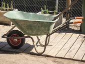 picture of wheelbarrow  - old tatty green wheelbarrow with red wheel and orange handles - JPG