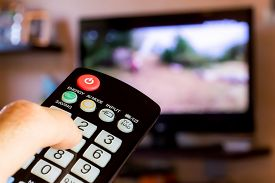 stock photo of tv sets  - use the remote control to change channels on Television - JPG