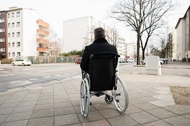 stock photo of wheelchair  - Rear View Of A Disabled Man On Wheelchair Looking At Street - JPG