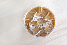 stock photo of cold drink  - top view cold coffee drink with ice on wood table - JPG