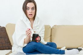 pic of temperature  - Upset woman with thermometer sick colds flu fever and migraine in bed with cup of tea or coffee - JPG