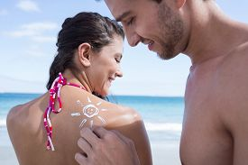 picture of sun tan lotion  - Handsome man putting sun tan lotion on his girlfriend at the beach - JPG