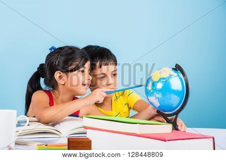 poster of indian boy and girl studying with globe on study table, asian kids studying, indian kids studying geography, kids doing homework or home work, two kids studying on table