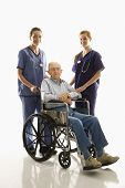 Two Caucasian females wearing scrubs with elderly Caucasian male in wheelchair.