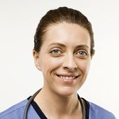 Head shot portrait of Caucasian woman doctor smiling against white background.