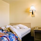 Interior shot of motel room with unmade bed and wall lamp.