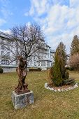 Постер, плакат: Bronze Woman Statue In The Park Cold Day Nobody In The Park Bronze Statue Surrounded By Firs S