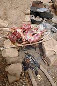 stock photo of dogon  - Goat cooking for a feast over a fire in a Dogon village in Mali - JPG