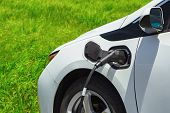 Electric Car Charging On Parking Lot With Electric Car Charging Station On Background Of Green Grass poster